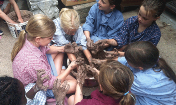 An overhead shot of a group of children working with clay and getting messy in the process