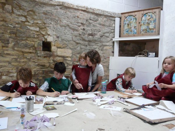 An image of a group of children of various ages and an adult. Each of them is engaged in drawing.