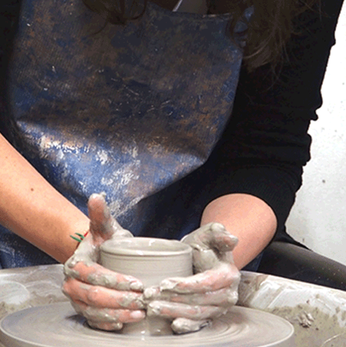 An Image of two hands working on a piece of clay on the pottery wheel