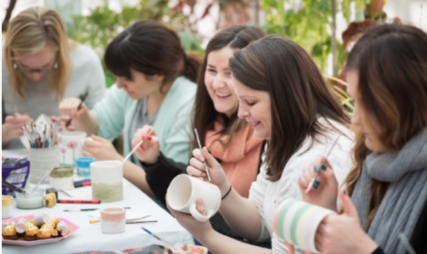 A photograph of a group of smiling friends painting mugs together